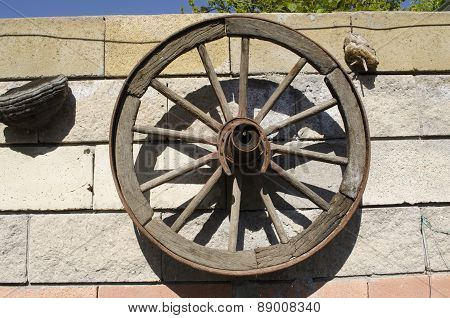 Old wooden wheel hanging on the stone wall in the garden