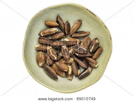 roasted pili nuts grown in Philippines, top view of ceramic bowl isolated on white