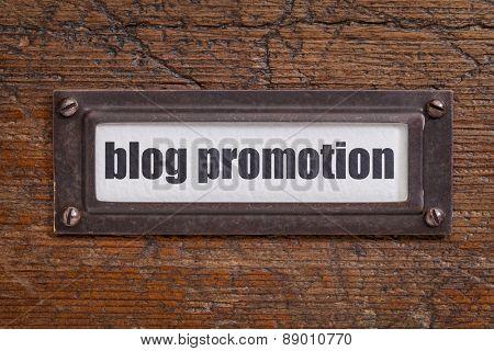 blog promotion- file cabinet label, bronze holder against grunge and scratched wood