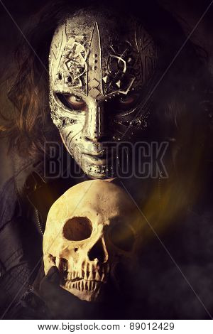 Mysterious man in iron mask holding skull. Steampunk. Fantasy. Halloween.