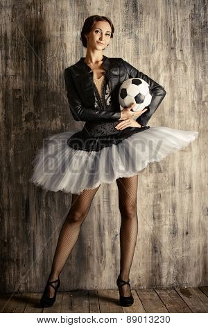 Portrait of a modern ballet dancer posing at studio over grunge background. Art concept.