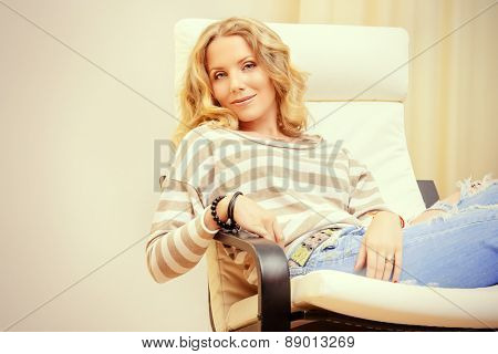 Beautiful happy young woman resting at home in a cozy armchair. Interior.