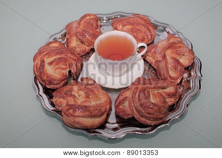 Sweet yeast rolls with cinnamon and sugar, a Cup of tea