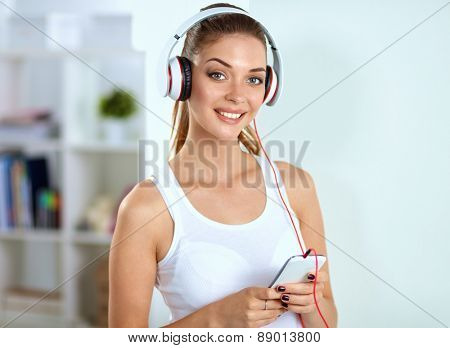 Woman with headphone listening music standing at home, isolated