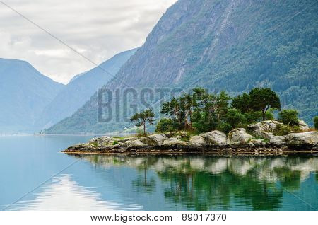 Small Island With Mountains Background At Norwegian Fjord