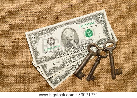 Us Dollar Banknotes And Vintage Keys On An Old Cloth