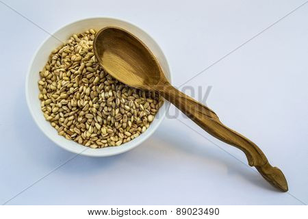 whole wheat in bowl and wooden spoon
