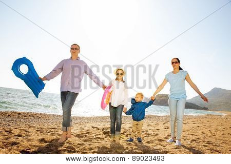 Full length of happy family holding hands while running on beach