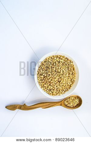 whole wheat in bowl and wooden spoon, vertical