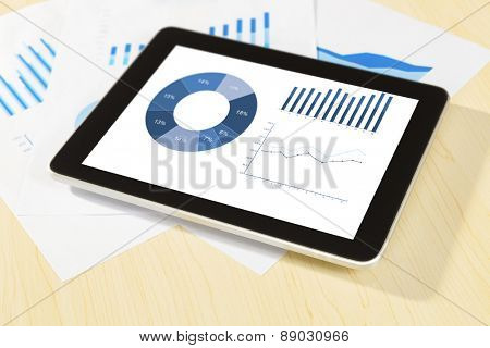 digital tablet, graph,chart on work table.