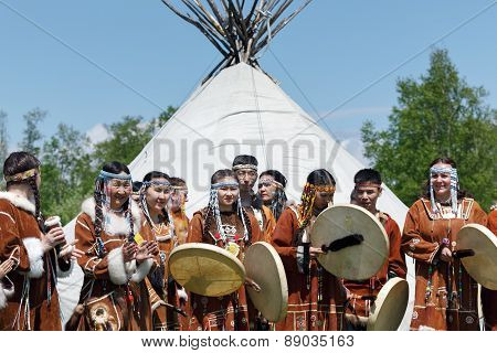 Group Of People In Clothing Aborigine Of Kamchatka Stand On Background At Yaranga