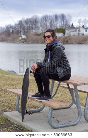 young adult female relaxing with longboard in a park