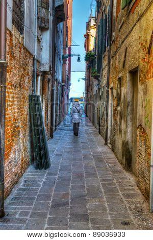 Woman Walking In An Old Backstreet