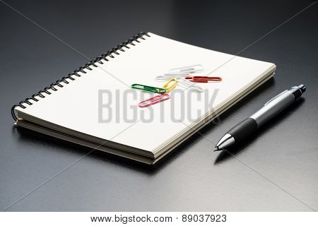 Notebook With Pen On Black Table