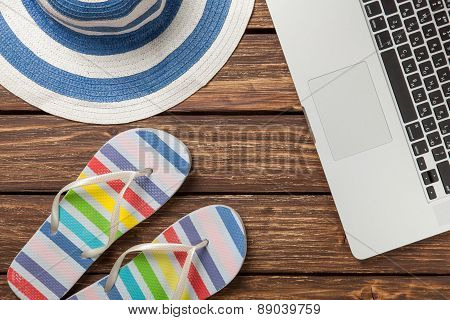 Hat And Laptop On Wooden Table.