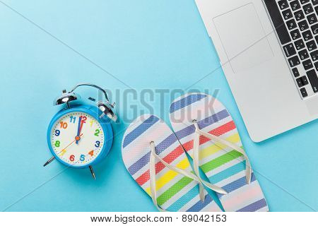 Alarm Clock With Flip Flops Near Notebook