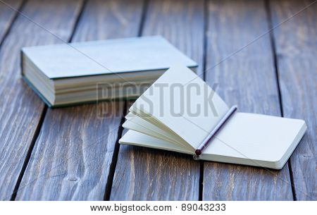 Notebook And Book On Background