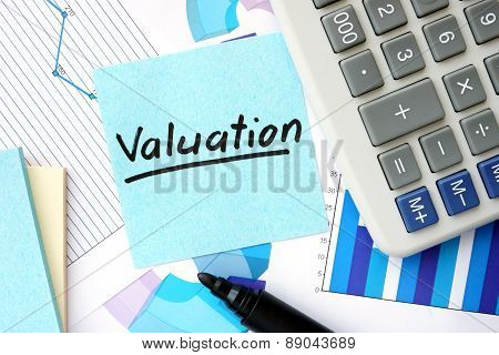 Papers with graphs, calculator and Valuation concept.