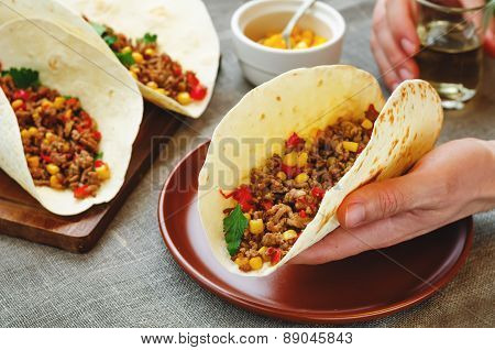Man Holding Tacos With Meat, Corn And Peppers