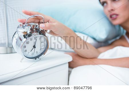 Sleepy young woman in bed extending hand to alarm clock at home in the bedroom
