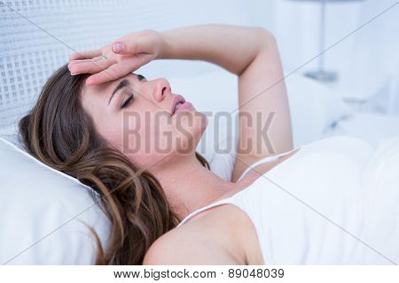 Sick woman touching her forehead at home in the bedroom