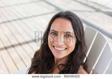 Pretty brunette sitting on a chair and smiling at camera in patio