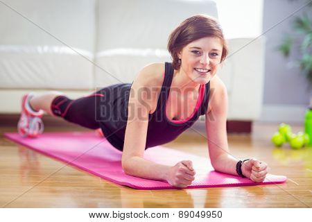 Fit woman doing plank on mat at home in the living room