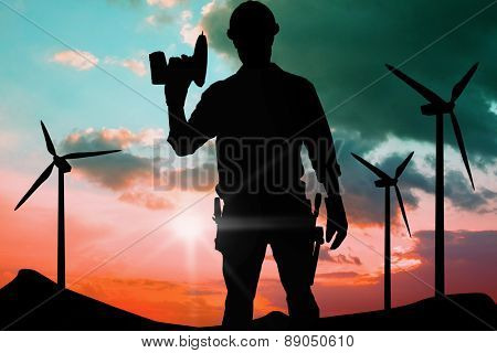 Confident male repairman holding drill machine against blue and pink sky
