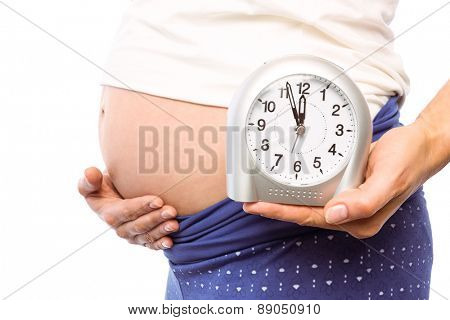 Pregnant woman showing clock and bump on white background
