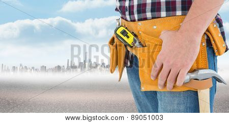Close-up of male repairman wearing tool belt against city on the horizon