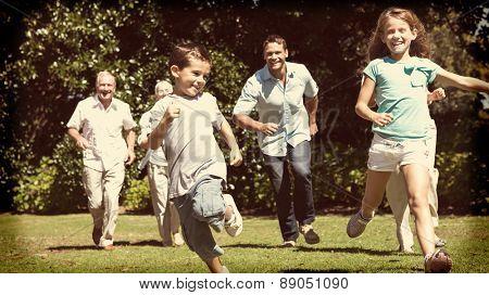 Happy multi generation family racing towards camera in a park
