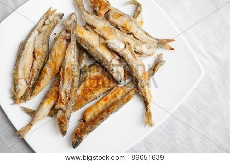 Pile Of Fried Smelts Fish Lays On A White Plate, Closeup Photo With Selective Focus