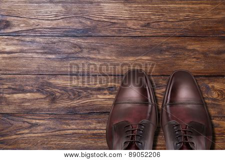 Classic male brown leather shoes on wooden background
