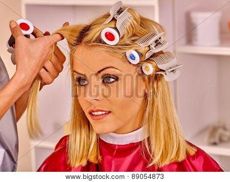 Happy woman wear hair curlers on head in barbershop.