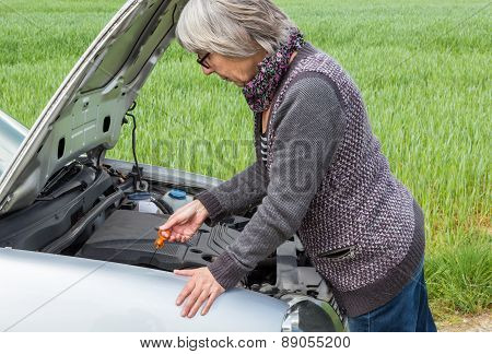 Senior Woman Looks After The Oil Level In The Car