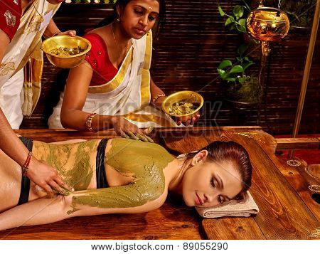 Young woman having body Ayurveda spa massage. Green mud.