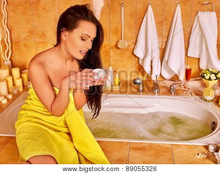 Woman applying moisturizer at bathroom. Looking on hands.