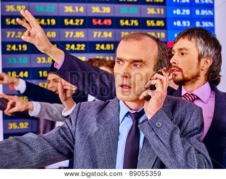 Group business people with  stock exchange board in office. Man in foreground.