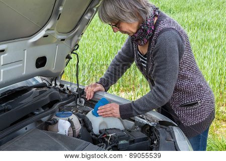 Senior Woman Looks After The Water Level On The Car