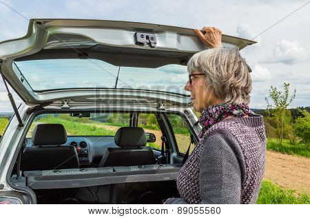 Senior Woman Opens The Trunk Of The Car
