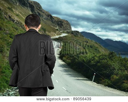 Rear View Businessman Walking On Mountain Road With Cloudy Sky