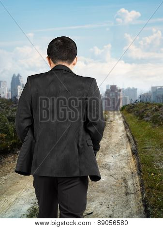 Rear View Businessman Walking On Trail To City With Cityscape