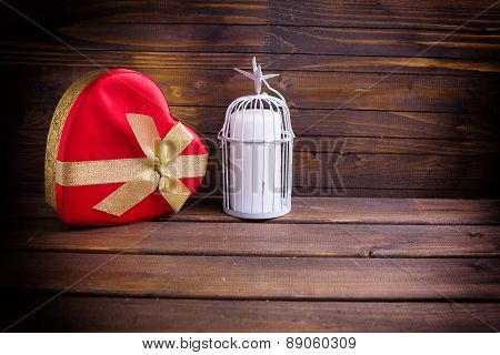 Festive Gift Box And Candle In Decorative Bird Cage