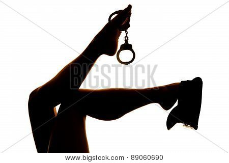 Silhouette Of Woman Legs Handcuffs And Hat