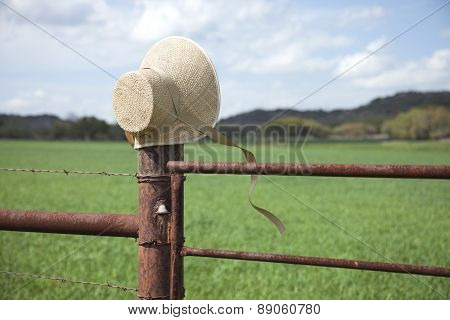 Old Fashioned Straw Bonnet On Fence Post In Texas Hill Country