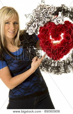 Woman Holding Heart Wreath Pointing
