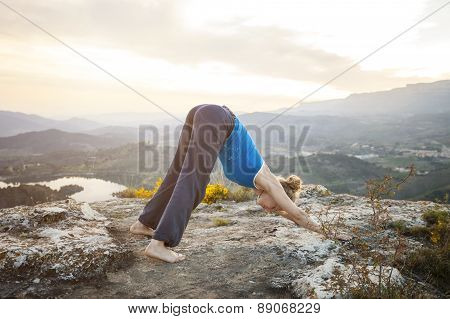 Woman performing downward dog yoga pose outdoors