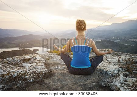 Young woman sitting in asana position on a rock