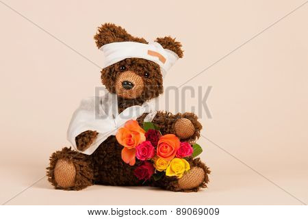 Stuffed hand made bear with pain plaster and flowers isolated over white background