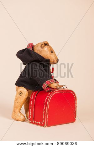 Vintage bear with coat and suitecase on beige background